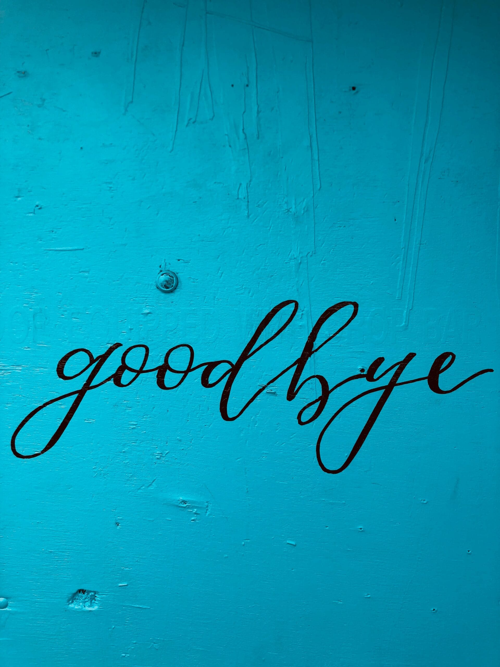 "the word ""goodbye"" on a blue wall, inviting someone to leave because they are no longer a good fit for your studio"