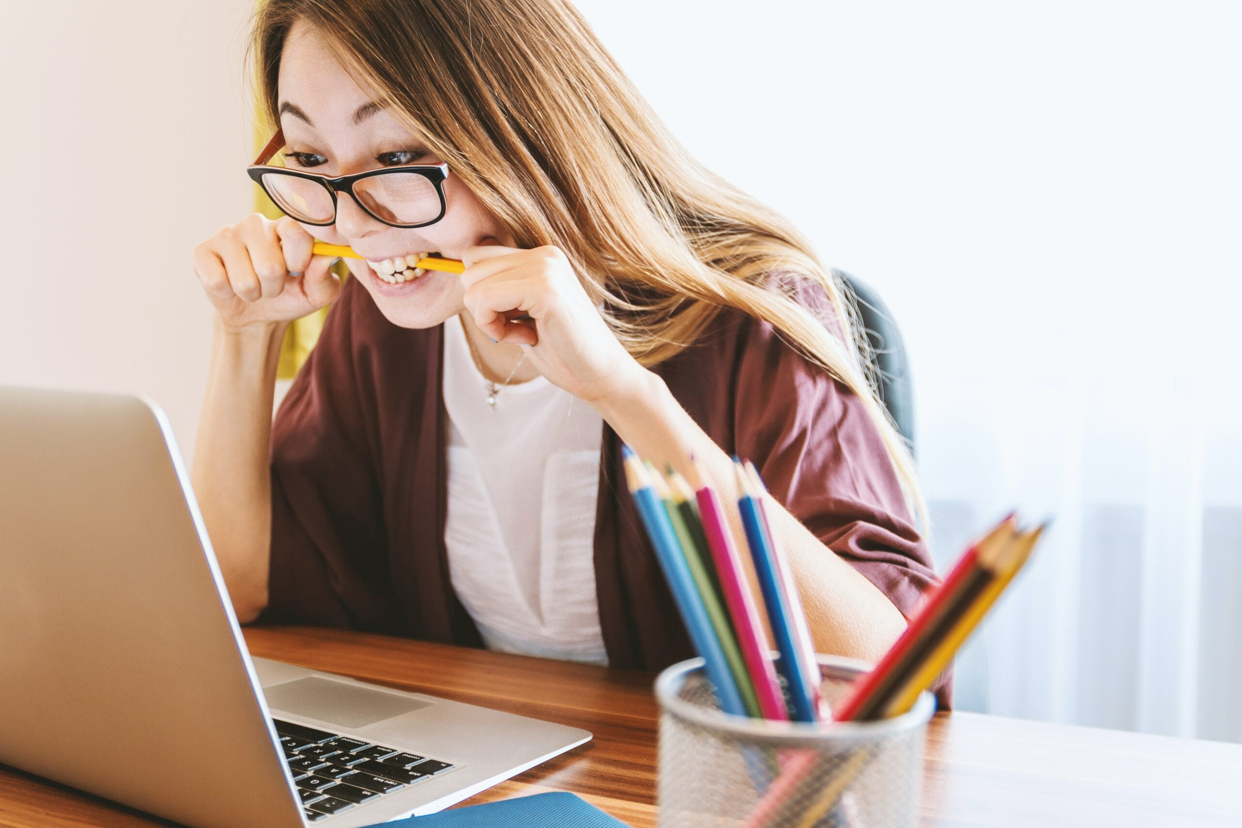 woman in glasses biting a pencil because she is worried about marketing needs and strategy